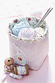 Balls of wool and knitting needles in pink basket next to vintage reels of yarn