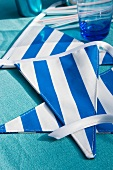 Blue and white striped bunting and drinking glass on blue tablecloth