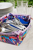 Patterned plastic container of cutlery in front of stacked plates and glasses on tablecloth in garden