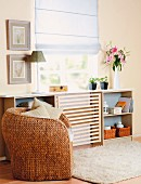 Wicker armchair in front of sideboard with DIY panel of wooden laths mounted in middle