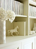 Detail of magazines, vase of flowers and horse figurine in white bookcase