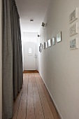 Narrow hallway with wooden floor leading to white front door with window