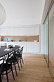 Schwarzer Esstisch mit Thonetstühlen auf Dielenboden vor offener Küche mit eingebauter Küchenzeile in Nische