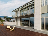 Zwei Klappstühle auf der weitläufigen Terrasse eines modernen Wohnhauses mit Panoramafenstern