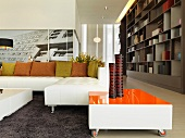 Living room with white sectional sofa with green and orange throw pillows