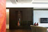 A dark built-in cupboard with illuminated niche for decorative vases