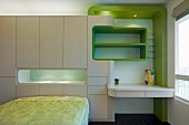 Futuristic wall unit with recessed shelves and desk and green accents