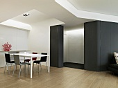 Moderne Tischgarnitur und eine schwarze, leicht abgerundete Wand im futuristisch angehauchten Esszimmer