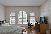 Home office desk with a giant flat screen TV in a bedroom with three arched windows