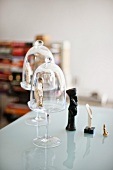 Small figurines and bell jars on a glass table