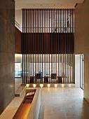 Minimalistischer Vorraum nach oben offen und Blick durch transparenten Raumteiler aus Holzlamellen in Essbereich
