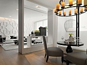 Schwarzer Bistrotisch unter Deckenkerzenleuchter in modernem Salon und Blick durch rahmenartige Öffnung ins Wohnzimmer
