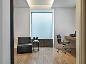 Blick durch Öffnung in minimalistischen Raum mit Ledersessel und Arbeitsecke