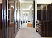 Kommode und Einbauschränke aus gleichem Holz in modernem Vorrraum mit raumhohen Durchgang und Blick in Wohnraum