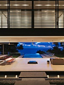 Grandioser Blick in der Abenddämmerung vom offenen puristischen Wohnbereich aus über einen Infinity-Pool auf den Pazifik
