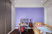 Bed in front of a window with a fabric roller blind and writing desk in front of a lavender wall in a small child's bedroom