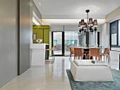 Offener Wohnraum mit rundem Essplatz unter klassisch modernem Kronleuchter in zeitgenössischer Architektur