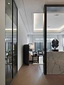 Blick durch den offenen, modernen Wohnraum auf hellen Holzboden und schwarzweisses Interieur