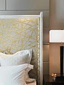 weiße Kissen vor dem dekorativ gestalteten Kopfteil eines Bettes