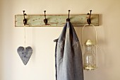 Heart ornament, jacket and lantern hanging from old coat rack