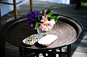 Pistachios and a vase of flowers on a side table