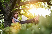 Smiling woman using laptop in tree
