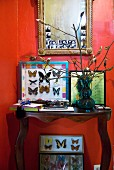 Red wall as backdrop for collection of framed butterflies and antique mirror with passport photographs stuck in frame