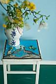 Blumenvase aus Porzellan mit floralem Muster auf einem Holzhocker mit aufgemaltem Vogelbild