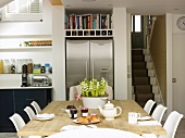 Set breakfast table in open-plan kitchen with stainless steel side-by-side fridge and view of staircase
