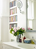 Bouquet of peonies and bathroom utensils on washstand next to bookcase built into wall