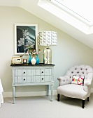 Table lamp with patterned lampshade on vintage chest of drawers and antique, upholstered armchair under sloping ceiling