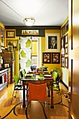 Sunny yellow kitchen with antique dining table, photo portraits on wall and curtain with pattern of gingko leaves