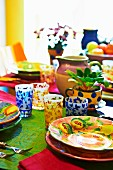 Colourful dining table with brightly painted ceramic crockery and patterned glasses