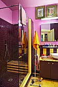 Dark purple shower cubicle in idiosyncratic bathroom with yellow accents and gold-painted door