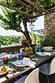 Gedeckter Tisch auf rustikaler Terrasse mit Pergola
