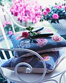 Roses and secateurs on cushions and vintage style, white, metal chair in front of plant pots