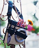 Garden tools in a tool belt hanging on decorative metal work