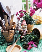 Garden gnome between carnations in a pot and garden tools in a woven metal flower box