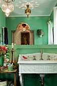 Antique-style sink in bathroom with green walls