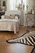Chaise longue next to side table and zebra-skin rug on parquet floor in bedroom