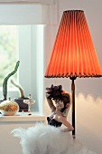 China doll of dancer next to lamp with lampshade