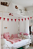 White canopied bed with pink scatter cushions and blanket in girl's bedroom