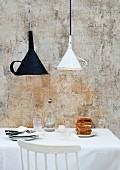 Old kitchen funnels used as unusual lampshades above breakfast table