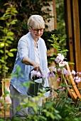 Mature woman watering her garden