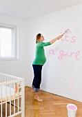 Schwangere Frau bemalt die Wand im Kinderzimmer