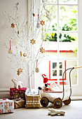 Various Christmas presents, toys and gifts in dolls' pram; Christmas biscuits as decorations on small, white-painted tree
