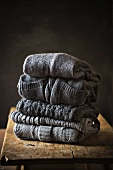 Five Grey Sweaters Stacked on a Wooden Table