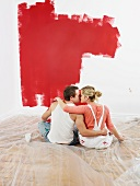 Küssendes Pärchen vor frisch gemalerter Zimmerwand