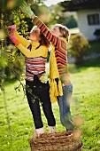 Zwei junge Frauen beim Apfelpflücken im herbstlichen Garten