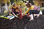 Zwei junge Frauen bei der Gartenarbeit im herbstlichen Garten
